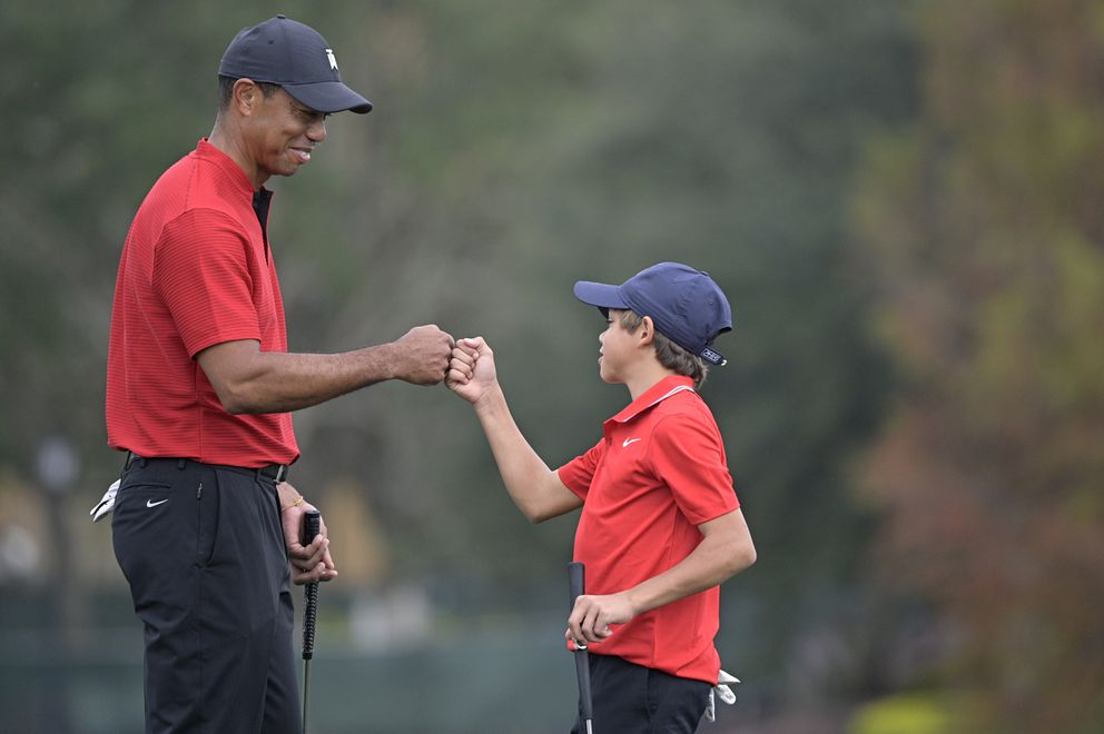 Tiger Woods, left, shares a fist-bump with his son Charlie after putting on the 18th green during the final round of the PNC Championship golf tournament, Sunday, Dec. 20, 2020, in Orlando, Fla. (AP Photo/Phelan M. Ebenhack)