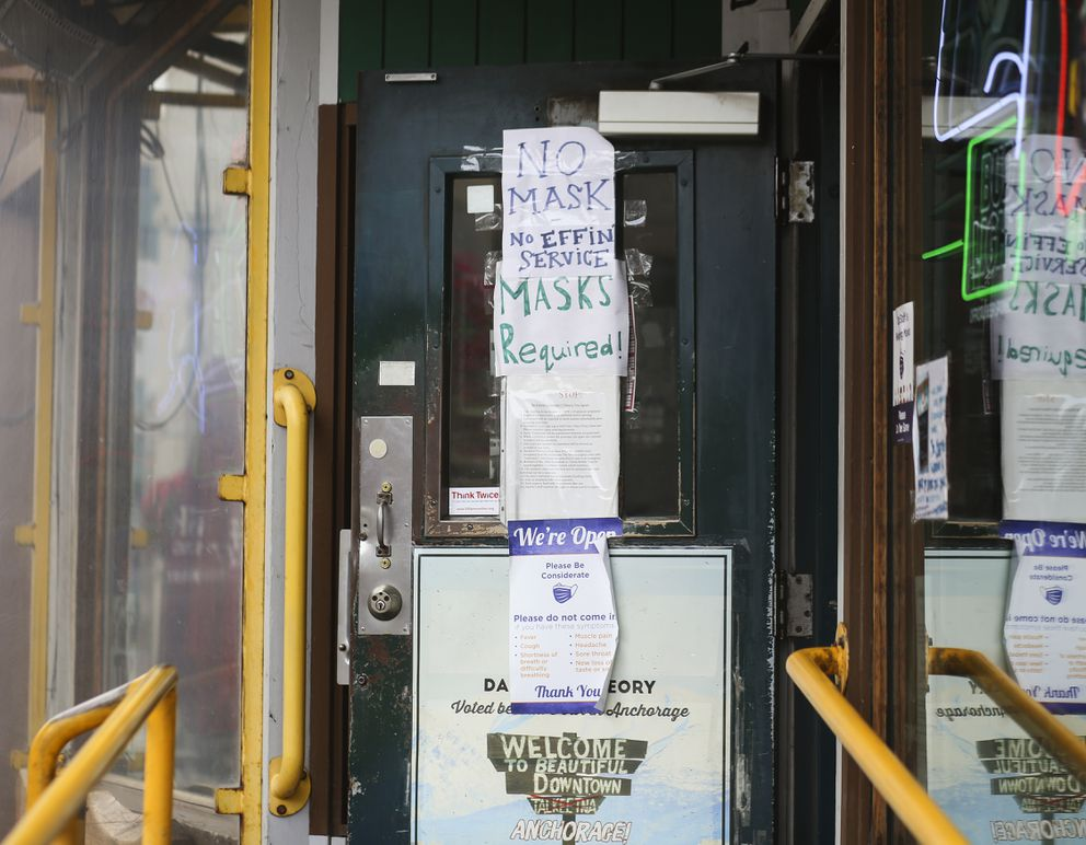 Mask requirement signs are taped to the entrance of Darwin's Theory in Anchorage on July 31, 2020. (Emily Mesner / ADN)