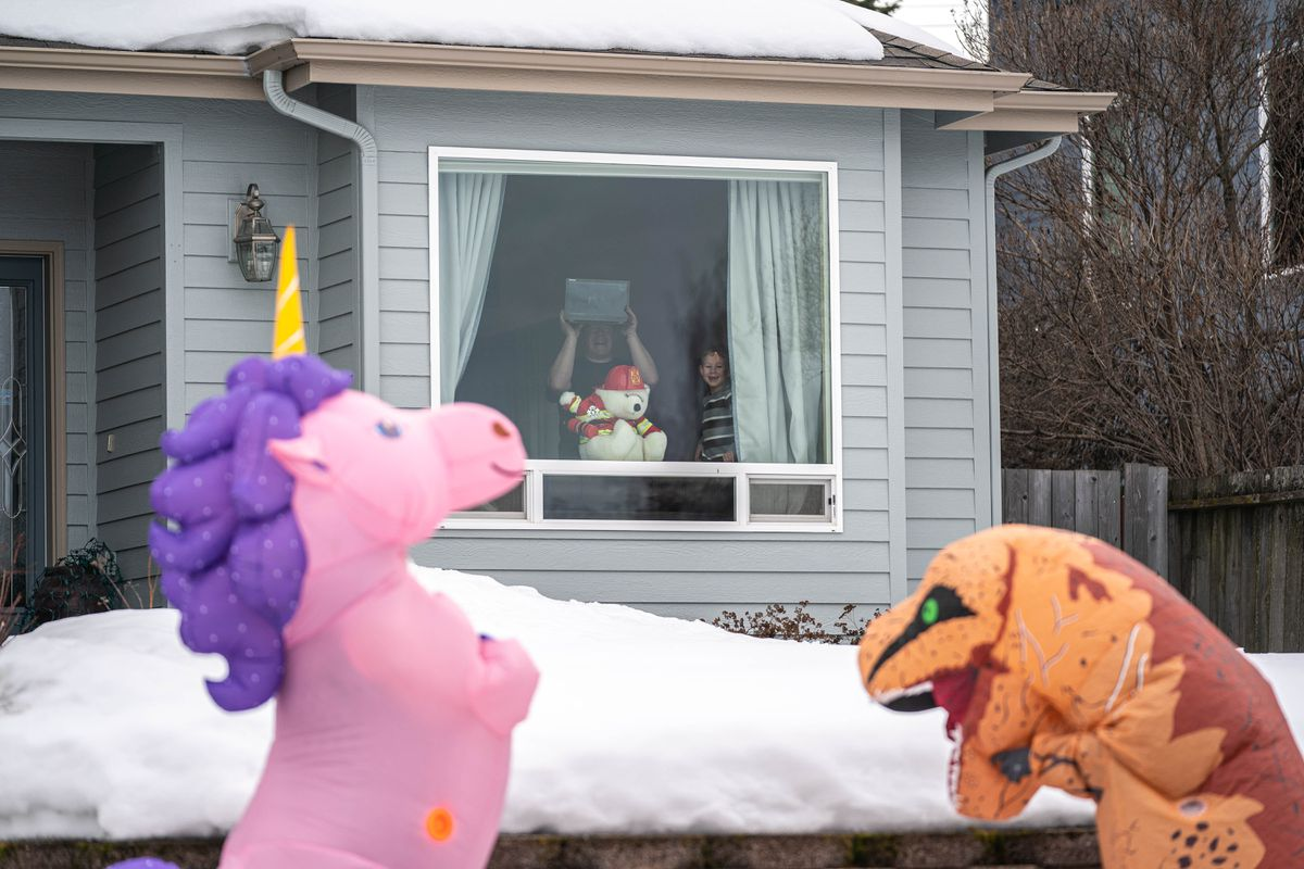 Craig Richards and his son Cameron, 6, watch from their window as Christine Hohf, wearing a unicorn costume, and Andi Correa, wearing a dinosaur costume, walk through South Addition on Wednesday, March 25, 2020 in Anchorage. Hohf, who works as a scrub tech at a surgery center, said her hours were cut due to elective surgeries being put off because of the coronavirus pandemic, and she wanted to do something that would make people smile. (Loren Holmes / ADN)