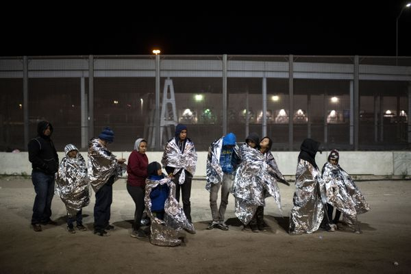 Migrant families wrapped in mylar blankets stand in line waiting to be loaded into a Border Patrol transport van to take them to a nearby holding facility in El Paso, Texas on Feb. 22, 2019. MUST CREDIT: Washington Post photo by Carolyn Van Houten