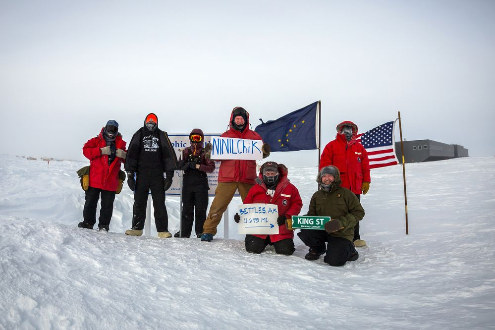 A group of current and former Alaskans are wintering at the Amundsen Scott South Pole Station in Antarctica. They got together for a 150th Alaska Day celebration and took some photos at the Geographic Pole Marker with the Alaskan Flag to honor the occasion, Oct. 18, 2017. From left to right: Robert Schwarz, Gavin Chensue, Catherine Dudley, Michael Pintur, Rick Osburn, Eric Hansen, Zachary Kinberg. (Photo by Hunter Davis)