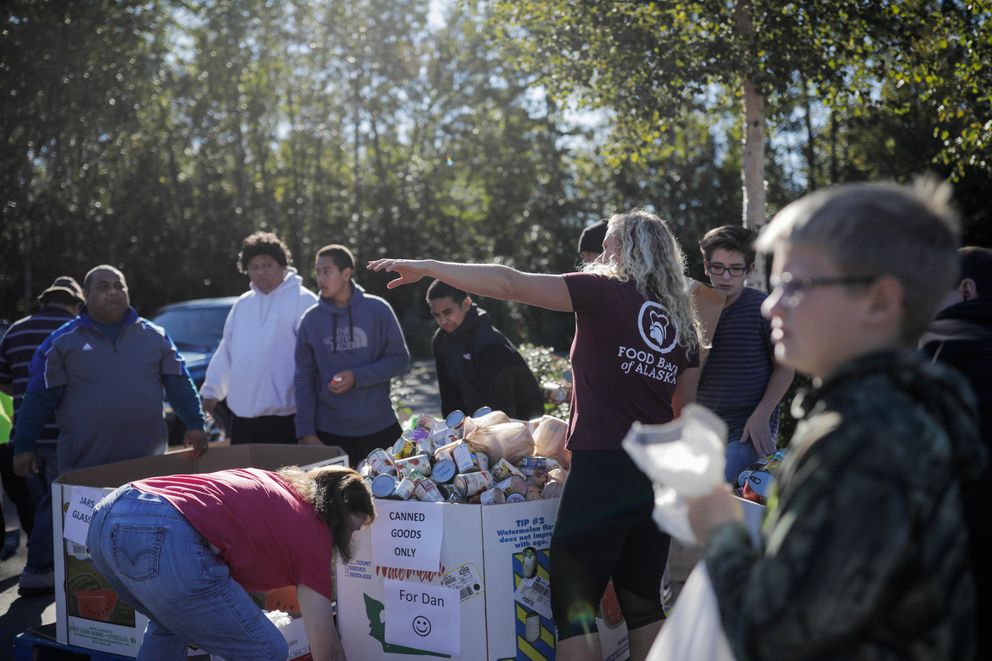Krista Milliken, volunteer coordinator for the Food Bank of Alaska, helps volunteers sort donated food on Saturday, Sept. 10, 2016. The Feeding Our Neighbors food drive was organized by the Church of Jesus Christ of Latter-day Saints. (Loren Holmes / Alaska Dispatch News)