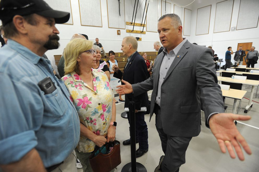 Sen. Mike Shower, R-Wasilla, right, and Rep. Mark Neuman, R-Big Lake, center, speak to folks after the legislative special session at Wasilla Middle School on Monday, July 8, 2019. (Bill Roth / ADN)