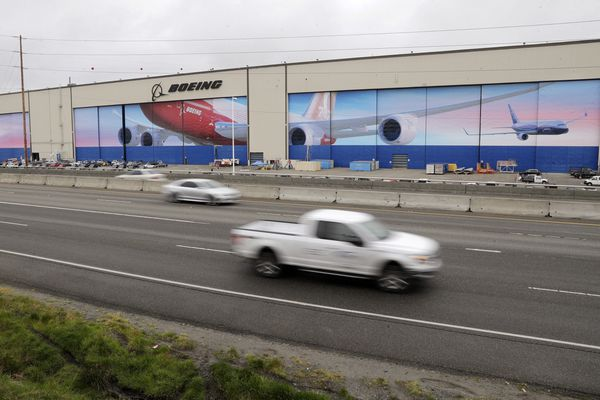 Traffic flows past the massive Boeing airplane production plant Tuesday, April 21, 2020, in Everett, Wash. Boeing this week is restarting production of commercial airplanes in the Seattle area, putting about 27,000 people back to work after operations were halted because of the coronavirus. (AP Photo/Elaine Thompson)