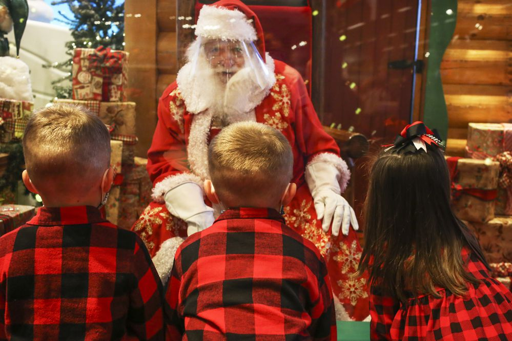 Mitchell Turpin, left, Mason Turpin, center, and Meredith Turpin, right, talk with Santa Claus at the Bass Pro Shops on Mountain View Drive in Anchorage on Friday, Nov. 27, 2020. (Emily Mesner / ADN)