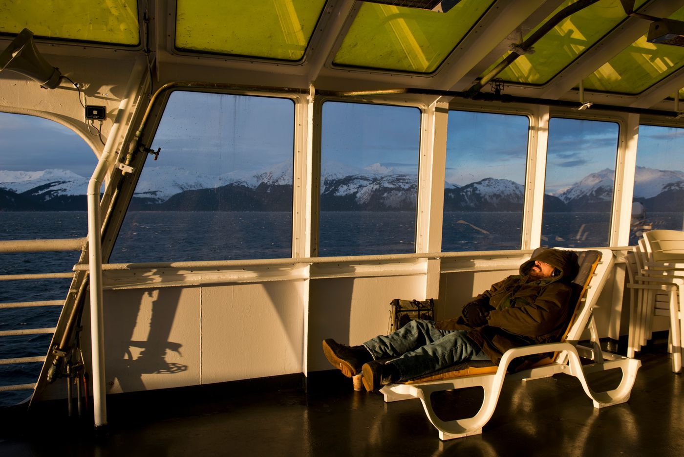 A passenger rests in the solarium of the ferry LeConte on January 22, 2017. (Marc Lester / Alaska Dispatch News)
