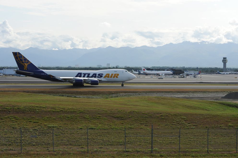 An Atlas Air Boeing 747-400 freighter taxis past one of two sites at Ted Stevens Anchorage International Airport on Tuesday, July 16, 2019, where proposed air cargo expansion facilities would be constructed. (Bill Roth / ADN)