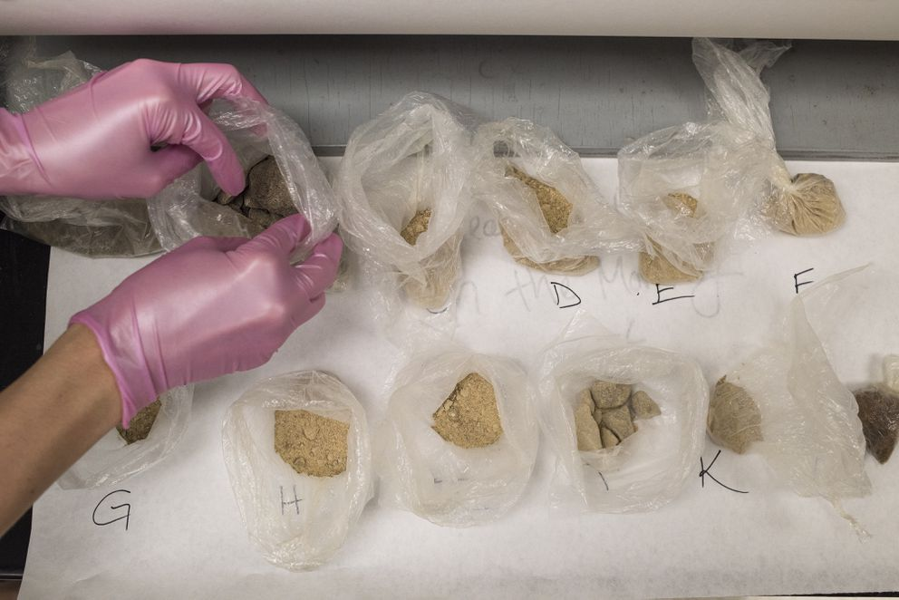 A forensic drug analyst opens baggies contains various types of heroin thatare being examined at the Hamilton County Coroners Crime Lab, in Cincinnati, Ohio, on Thursday. (Ty Wright / The New York Times)