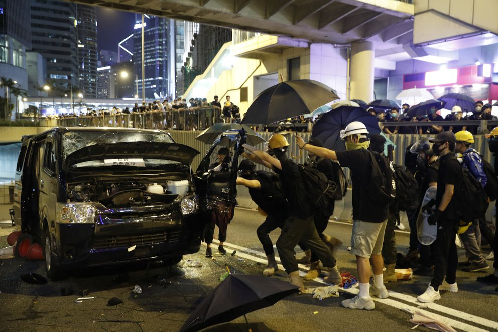 Protesters attack a van that apparently tried to drive at the protesters near a blocked road in Hong Kong, Sunday, July 21, 2019. Protesters in Hong Kong pressed on Sunday past the designated end point for a march in which tens of thousands repeated demands for direct elections in the Chinese territory and an independent investigation into police tactics used in previous demonstrations. (AP Photo/Vincent Yu)