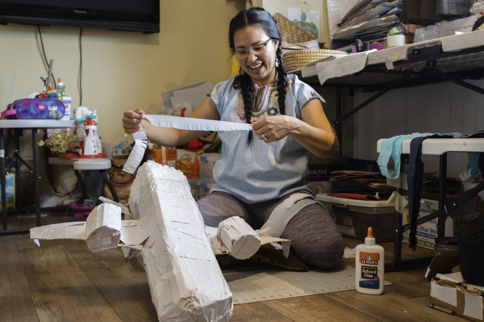 In this photo provided by Alaska Public Media, Carolina Tolladay Vadal is shown making a piñata in her home in Anchorage, Alaska, on April 14, 2021. After her piñata business ground to almost a halt during the pandemic, she rejuvenated her business by making large, coronavirus shaped piñatas. (Hannah Lies/Alaska Public Media via AP)