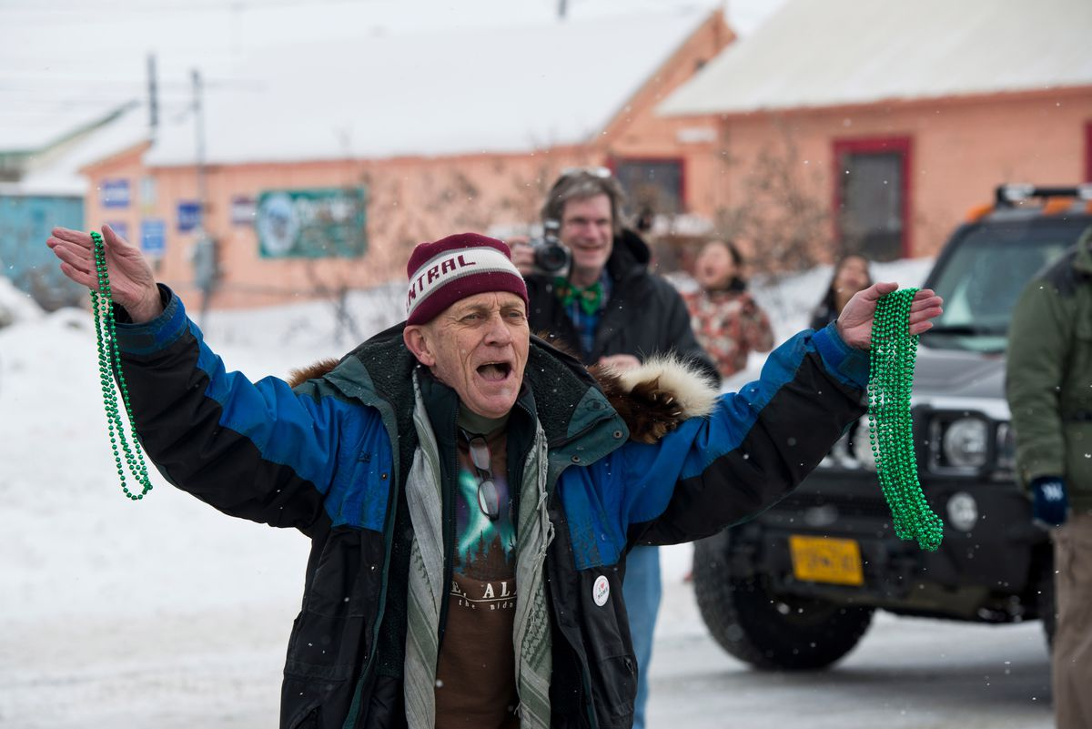 Nome Mayor Richard Beneville hands out green beaded necklaces at the St. Patrick's Day Parade on March 17, 2015. (Marc Lester / ADN)