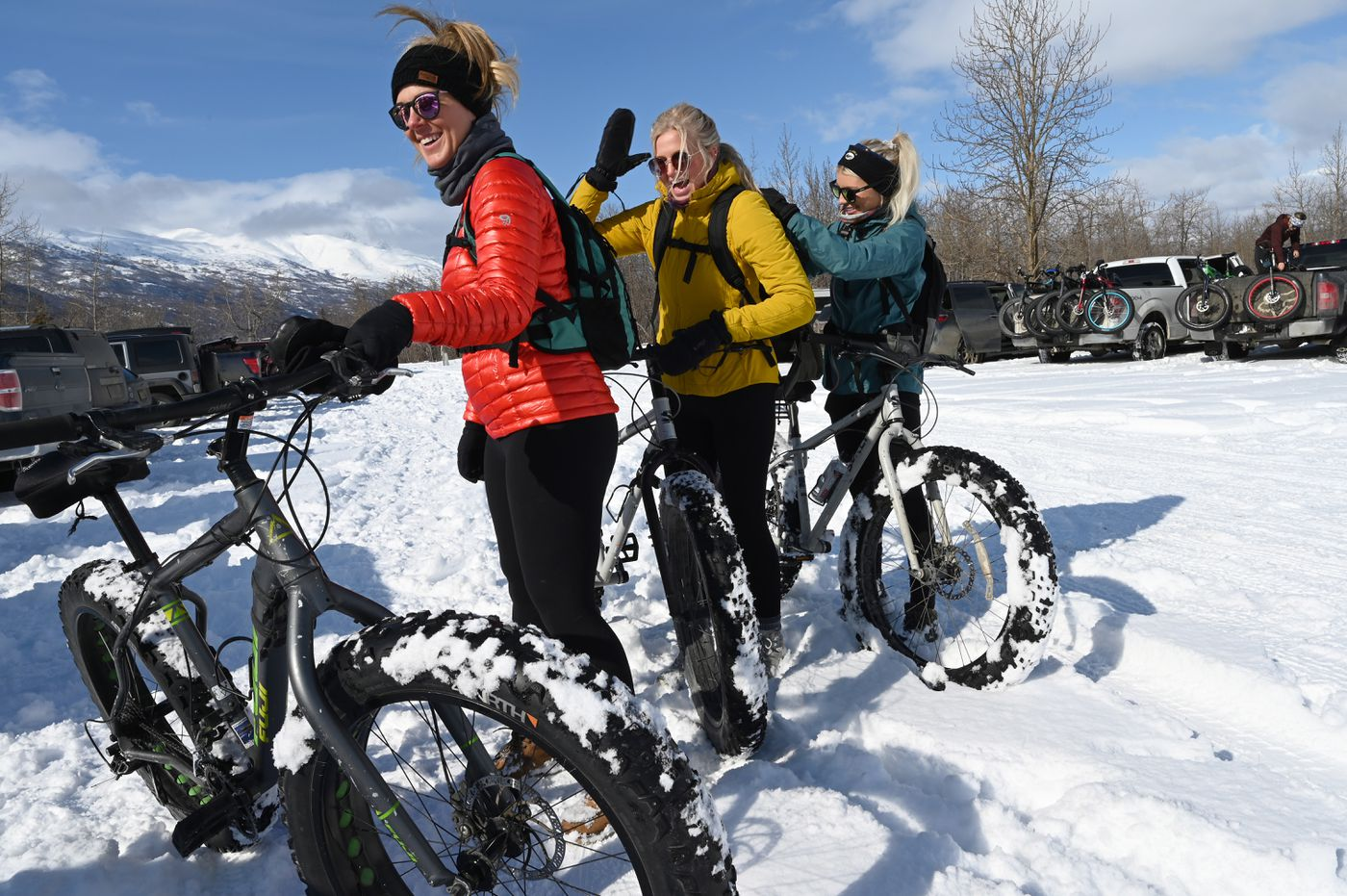 Erika Smith, left, Chelsea Gallagher, middle, and Jackie Housley prepare for their ride to the Knik Glacier in the parking area at Knik Glacier Tours Saturday, March 27, 2021. They were helping each other pack their backpacks. Their friendships began on Instagram. (Anne Raup / ADN)