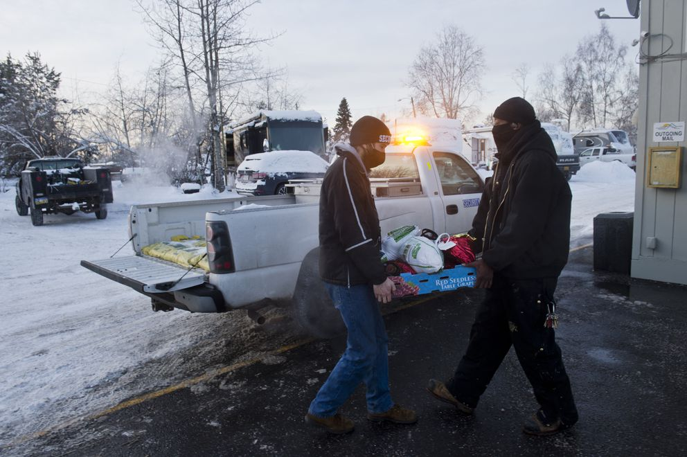 Andy Morckel, left, and Marcus Sims load hams and turkeys into a pickup truck to distribute to households. (Marc Lester / ADN)