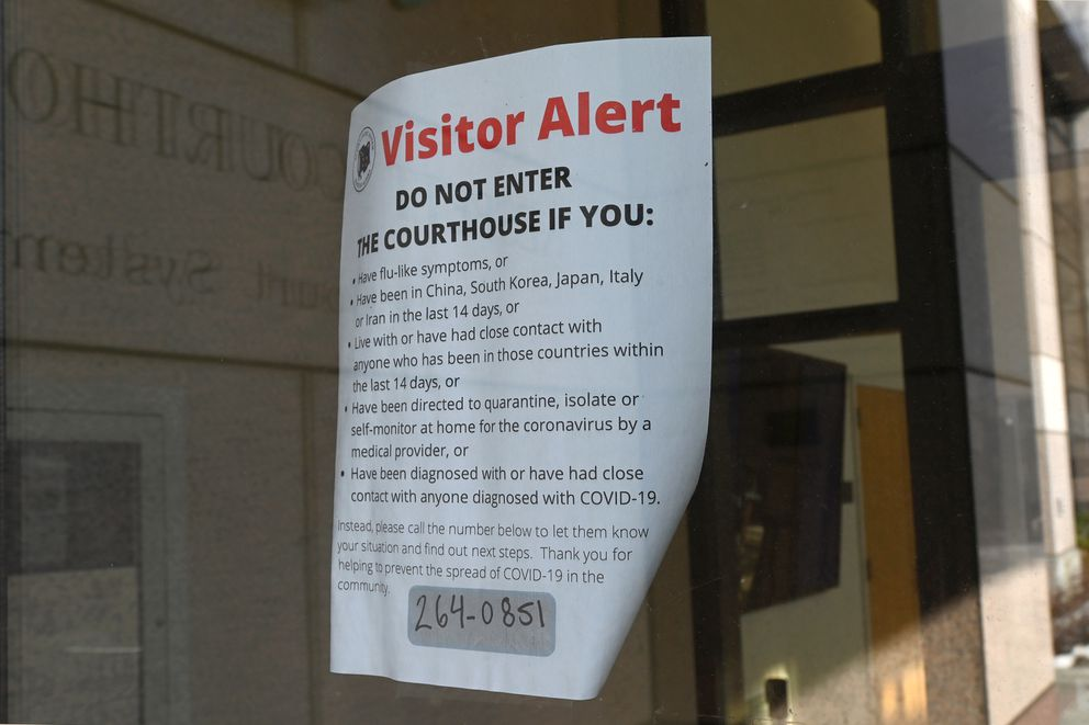 COVID-19 visitor alert posted on entrance doors to the Nesbett Courthouse in downtown Anchorage on Monday, March 23, 2020. (Bill Roth / ADN)