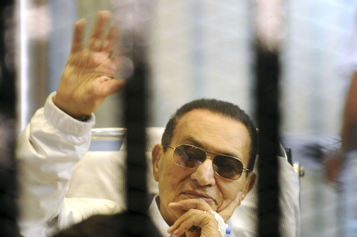 FILE - In this April 13, 2013 file photo, former Egyptian President Hosni Mubarak waves to his supporters from behind bars as he attends a hearing in his retrial on appeal, in Cairo, Egypt. On Wednesday, Dec. 26, 2018, two former Egyptian presidents appeared in the same Cairo courtroom. The 90-year-old Mubarak testified in a retrial of ousted Egyptian President Mohammed Morsi. Mubarak whose nearly three-decade rule was ended by a popular uprising in 2011, was seen walking into the courtroom with a cane along with his two sons Alaa and Gamal. (AP Photo, File)