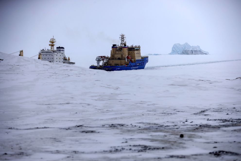 An Icebreaker makes the path for a cargo ship with an iceberg in the background near a port on the Alexandra Land island near Nagurskoye, Russia, Monday, May 17, 2021. (AP Photo/Alexander Zemlianichenko)