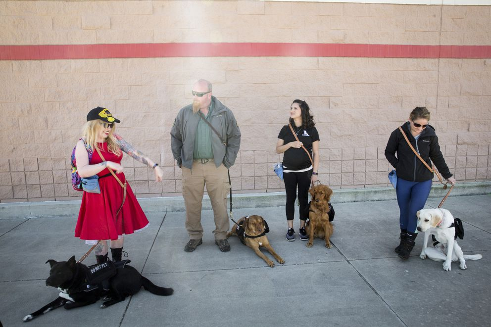 From left: Adrianna Ruark and her dog Crockett; Greg Wells and his dog Utah; Selena Hosier and her dog Zeebee; and Krista Shirey and her dog Bobbi split into groups of two before going into Target during K9s for Warriors training. (Photo for The Washington Post by Kile Brewer)