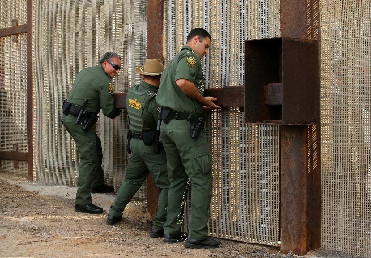 U.S. Border Patrol agents open a gate on the fence along the Mexico border to allow families separated in the two countries to embrace as part of Universal Children's Day at the Border Field State Park, Calif., on Nov.19.(Mike Blake / Reuters file)