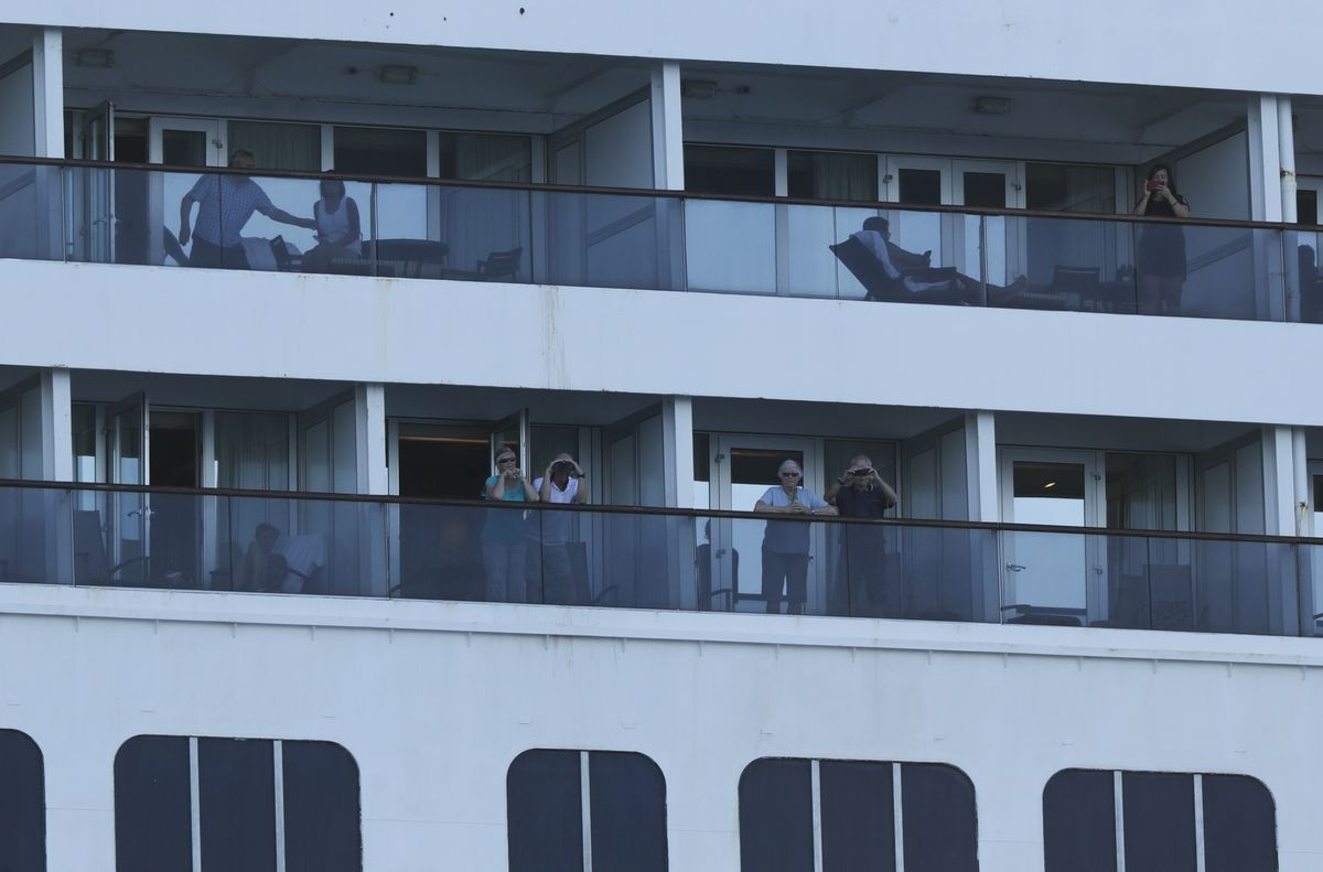 Passengers look out from the Zaandam cruise ship, anchored in the bay of Panama City, Friday, March 27, 2020. Several passengers have died aboard the cruise ship and a few people aboard the ship have tested positive for the new coronavirus, the cruise line said Friday, with hundreds of passengers unsure how long they will remain at sea. (AP Photo/Arnulfo Franco)