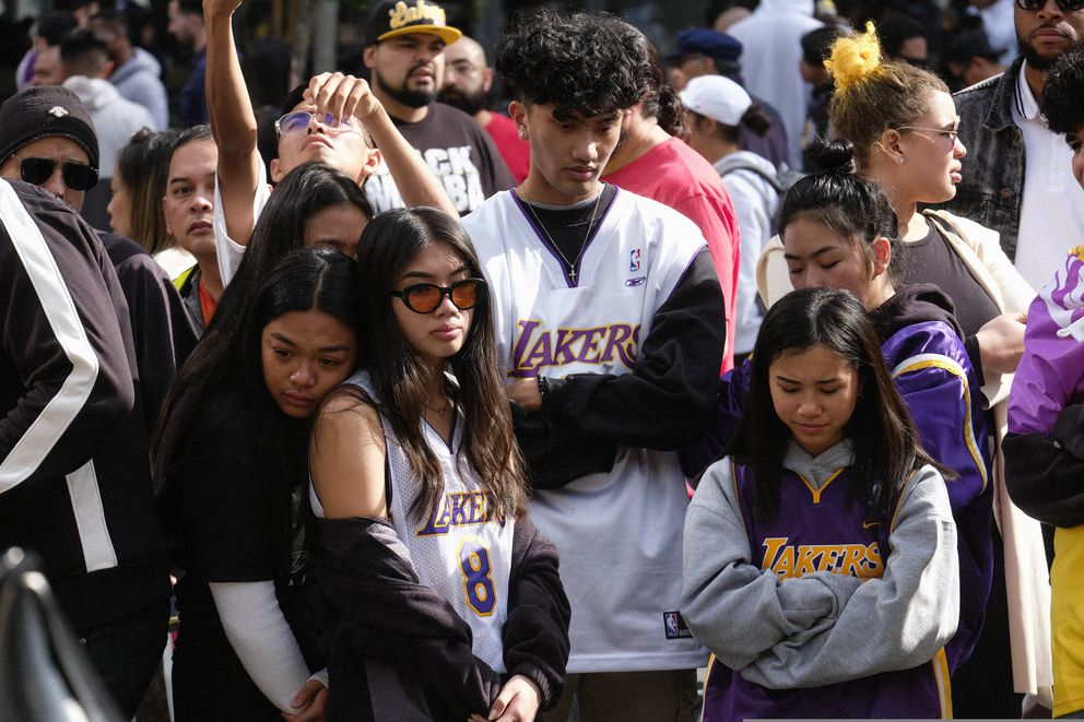 Fans gather at a memorial for Kobe Bryant near Staples Center Monday, Jan. 27, 2020, in Los Angeles. Bryant, the 18-time NBA All-Star who won five championships and became one of the greatest basketball players of his generation during a 20-year career with the Los Angeles Lakers, died in a helicopter crash Sunday. (AP Photo/Ringo H.W. Chiu)
