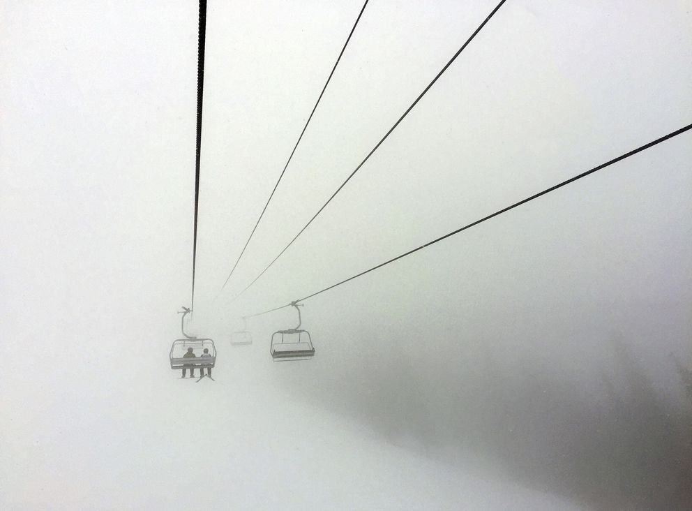 In this March 24, 2019 file photo, skiers ride a chair lift into a bank of fog at Colorado's Beaver Creek Resort. Resorts are trying to figure out how to safely reopen and are asking guests to embrace a new normal while skiing and snowboarding amid a pandemic. (AP Photo/Thomas Peipert, File)