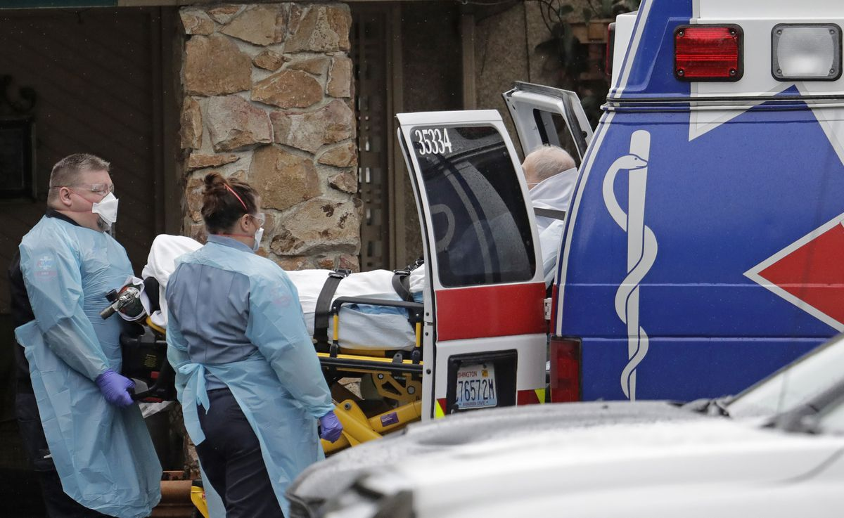 Ambulance workers move a man on a stretcher from the Life Care Center in Kirkland, Wash. into an ambulance, Friday, March 6, 2020. The facility is the epicenter of the outbreak of the the COVID-19 coronavirus in Washington state. (AP Photo/Ted S. Warren)