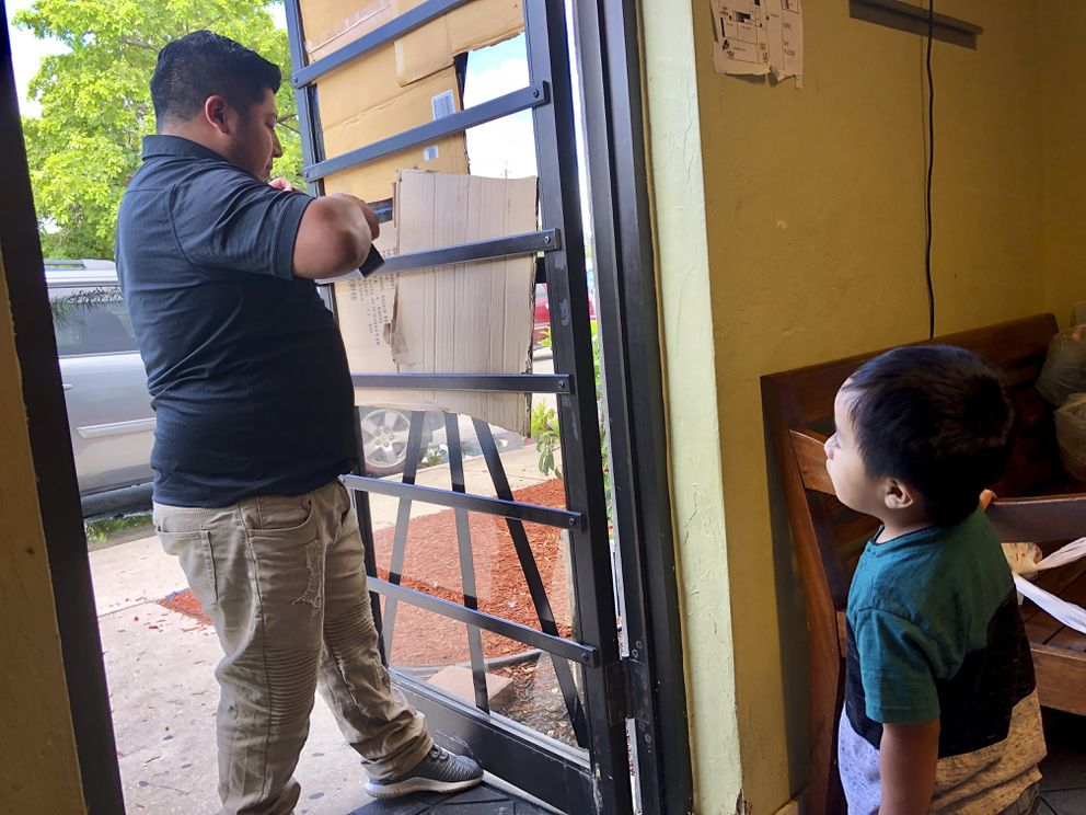 A volunteer of the center is tapes pieces of cardboard to the glass doors as women waited in line for help at the Guatemalan-Maya Center for immigrants on on Friday, Aug. 30, 2019 in Lake Worth, Fla. Charity groups are worried about vulnerable populations along the eastern coast, who were still in the cone of potential storm pathway forecast by the National Hurricane Center in Miami. (AP PhotoAdriana Gomez)