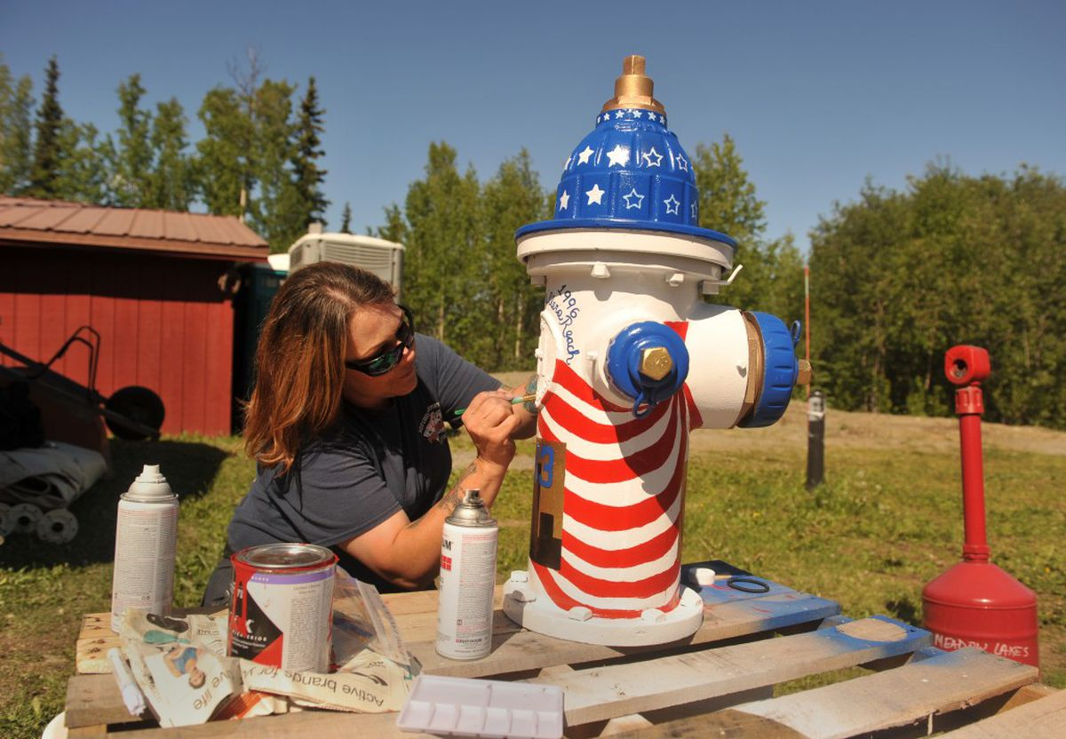 Hope Malidore, a firefighter at the West Lakes Fire Department in Big Lake, paints a fire hydrant in front of the station on Wednesday, June 8, 2016. (Bob Hallinen / Alaska Dispatch News)