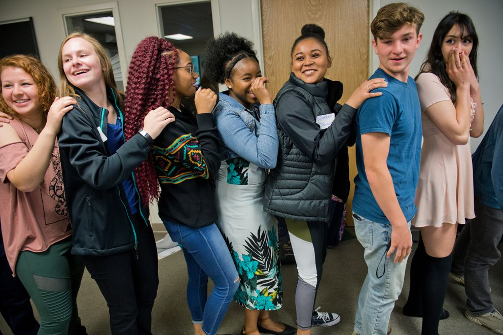 Joyah Cook, center, laughs with Nevaeh Long, third from left, and Yesmeen Dawson, fifth from left, during icebreaking exercises for students at Alaska Middle College School on Monday. The first day of the school year in the Anchorage School District was also the first day for its new program, Alaska Middle College School. (Marc Lester / Alaska Dispatch News)