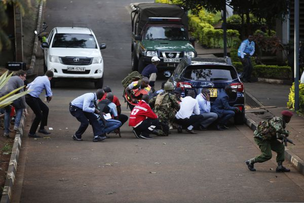 People take cover after an attack on a hotel, in Nairobi, Kenya, Tuesday, Jan. 15, 2019. Extremists launched a deadly attack on a luxury hotel in Kenya's capital Tuesday, sending people fleeing in panic as explosions and heavy gunfire reverberated through the complex. A police officer said he saw bodies,
