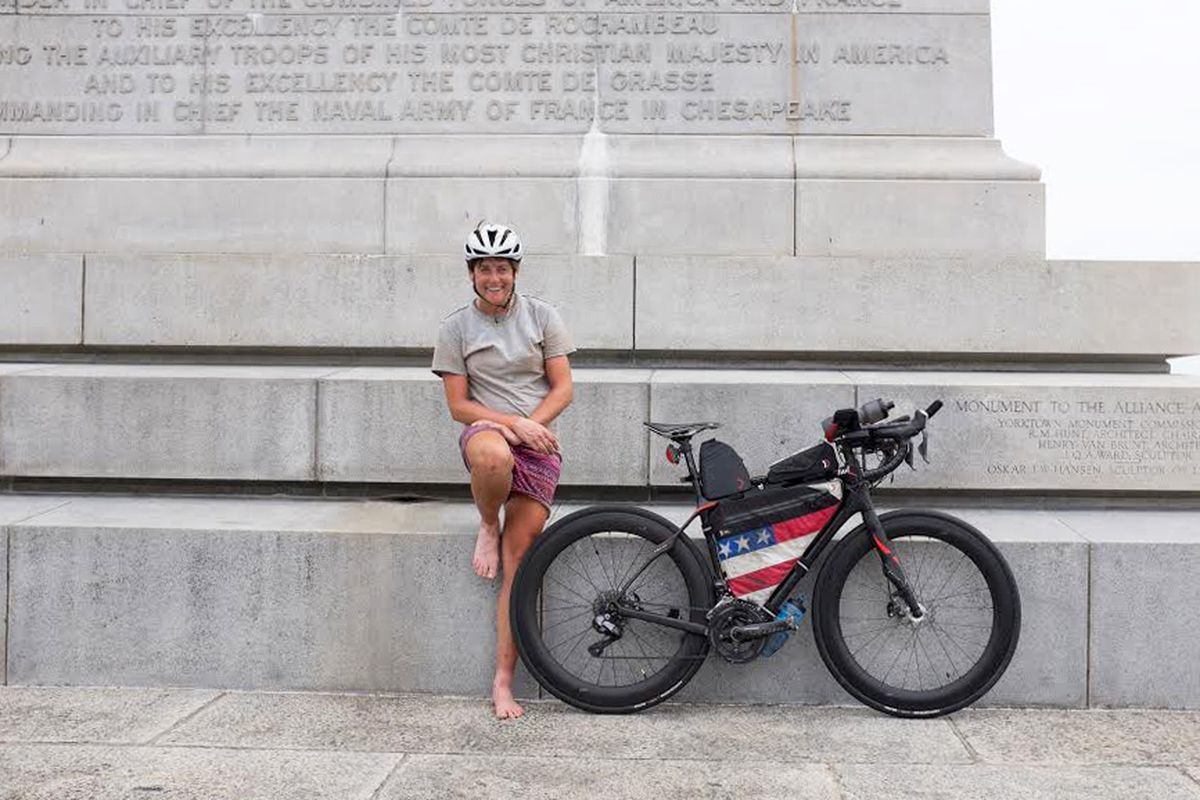 Cyclist Lael Wilcox of Anchorage relaxes at the Yorktown Victory Monument after she came from behind on the final day of an 18-day race Wednesday, June 22, 2016, to win the 4,200-mile Trans Am Bike Race. (Nicholas Carman)