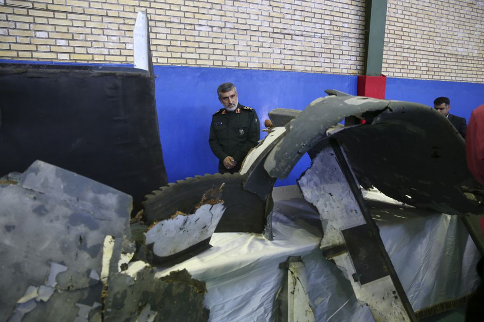 Head of the Revolutionary Guard's aerospace division Gen. Amir Ali Hajizadeh looks at debris from what the division describes as the U.S. drone which was shot down on Thursday, in Tehran, Iran, Friday, June 21, 2019. Major airlines from around the world on Friday began rerouting their flights to avoid areas around the Strait of Hormuz following Iran's shooting down of a U.S. military surveillance drone there, as America warned commercial airliners could be mistakenly attacked. Hajizadeh said on Friday, Iran had warned a U.S. military surveillance drone several times before launching a missile at it. (Meghdad Madadi/Tasnim News Agency/via AP)