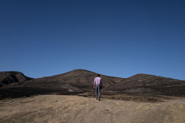 A man walks across a dried and burned out landscape, a result of the Real Fire, in Goleta, Calif. The Real Fire scorched more than 400 acres in mid-October but was quickly contained due to heightened awareness and readiness by local fire departments. MUST CREDIT: Washington Post photo by Michael Robinson Chavez