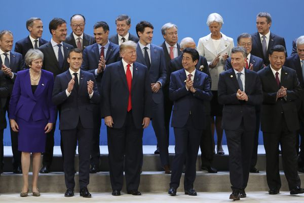 World leaders gather for a group photo at the start of the G20 Leader's Summit at the Costa Salguero Center in Buenos Aires, Argentina, Friday, Nov. 30, 2018. Bottom row from left are Britain's Prime Minister Theresa May, France's President Emmanuel Macron, President Donald Trump, Japan's Prime Minister Shinzo Abe, Argentina's President Mauricio Macri and China's President Xi Jinping. Behind are European Council's President Donald Tusk, the Netherlands' Prime Minister Mark Rutte, unidentified, Spain's Prime Minister Pedro Sanchez, unidentified, Canada's Prime Minister Justin Trudeau, unidentified, International Monetary Fund Managing Director Christine Lagarde, South Korea's President Moon Jae-in, unidentified, and Chile's President Sebastian Pinera. (AP Photo/Ricardo Mazalan)