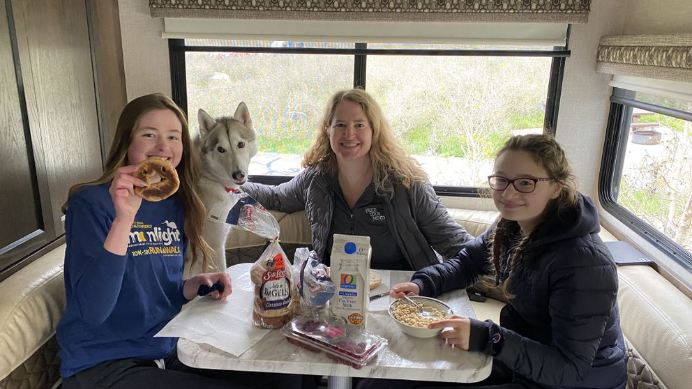 Madeline, Adelle and Carrie Lohse (and Miko, the husky pup) enjoy a camp breakfast in the RV. (Photo by Mike Lohse)