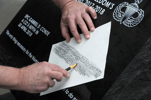 Eugene Bourdeau, Jr., who is the great uncle of Staff Sgt. David Thomas Brabander, creates an imprint from the incised letters of his name on the memorial outside the 4-25 Infantry Brigade Combat Team Headquarters on Joint Base Elmendorf-Richardson on Thursday, Nov. 7, 2019. (Bill Roth / ADN)