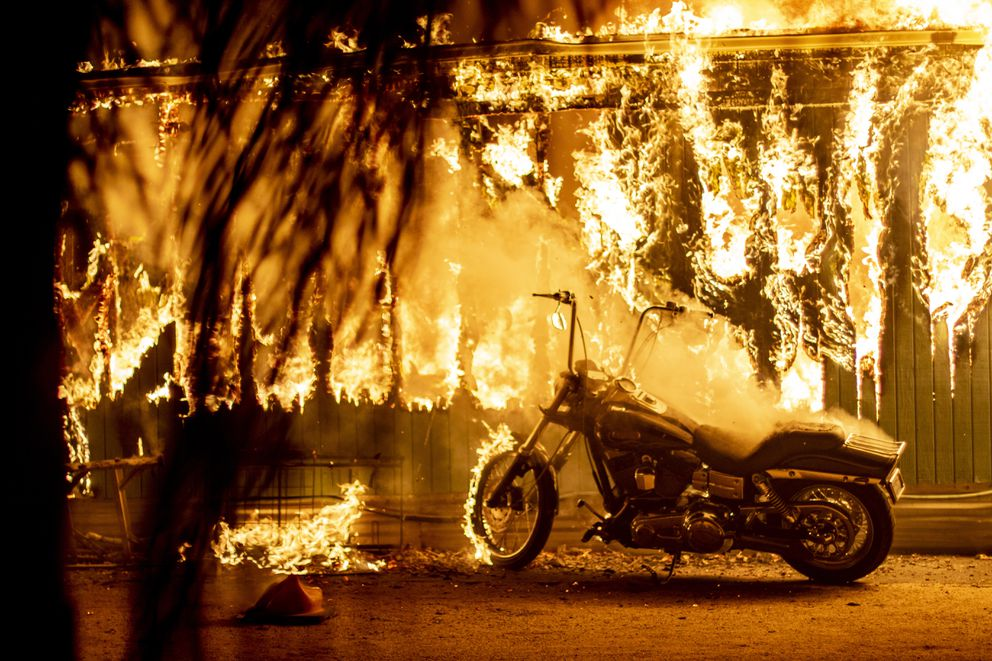 A motorcycle begins to catch fire outside an engulfed structure at a park for recreational vehicles in Malibu, California. Photo by Kyle Grillot for The Washington Post