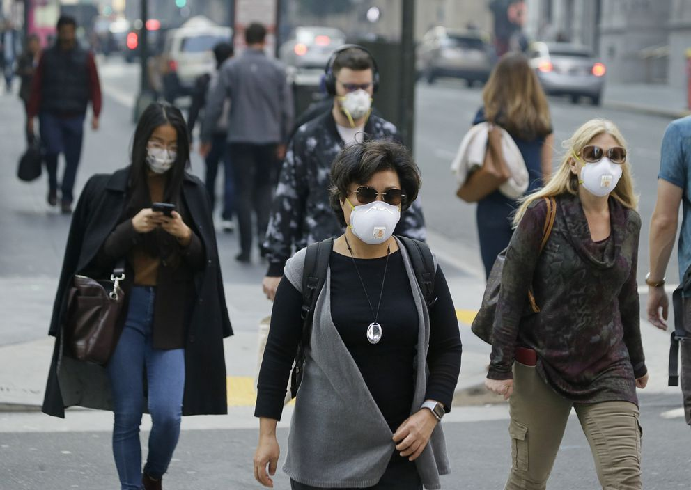 FILE - In this Friday, Nov. 9, 2018 file photo, people wear masks while walking through the Financial District in the smoke-filled air in San Francisco, as authorities issued an unhealthy air quality alert for parts of the San Francisco Bay Area as smoke from a massive wildfire drifts south. In 2017 and 2018, the nation had more polluted air days than just a few years earlier, federal data shows. While it remains unclear whether this is the beginning of a trend, health experts say it's a troubling development.(AP Photo/Eric Risberg)