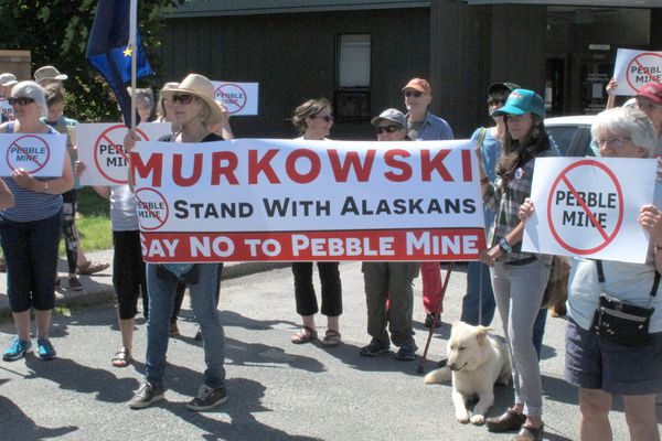 FILE - In this June 25, 2019 file photo, people gather outside U.S. Sen. Lisa Murkowski's office in Juneau, Alaska, to protest the proposed Pebble Mine. (AP Photo/Becky Bohrer, File)