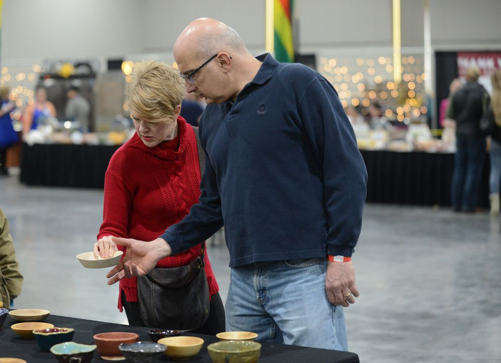 Dee Dee and Frank Feghali chose handmade bowls during the Empty Bowl Project at the Dena'ina Center. (Bob Hallinen / ADN)