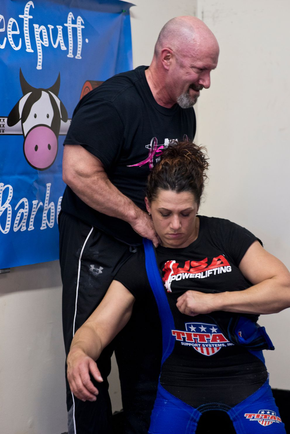 Priscilla Ribic is helped into her powerlifting suit by coach and husband Larry Maile. (Marc Lester / Alaska Dispatch News)