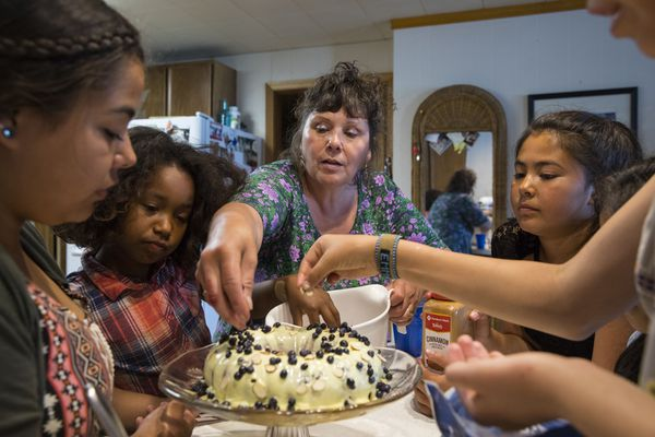 Children help Cynthia Erickson jazz up a lemon blueberry cake she made with a boxed cake mix, at her home in the small village of Tanana, along the Yukon River in central Alaska, July 18, 2017. In the small, mostly indigenous communities that dot rural Alaska, places accustomed to scarcity, box cake is a stalwart staple, the star of every community dessert table and a potent fundraising tool. (Ruth Fremson/The New York Times)