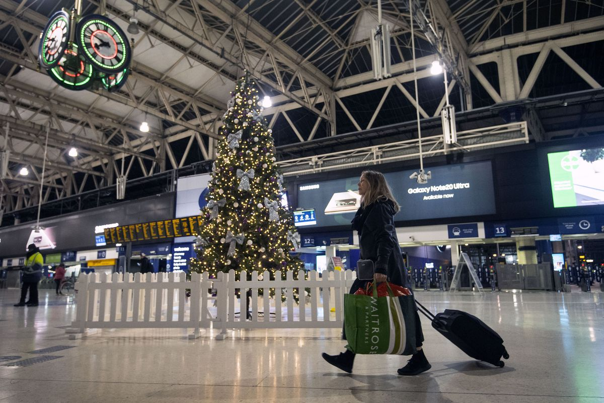 FILE - In this Sunday Dec. 20, 2020 file photo a woman pulls a suitcase past the Christmas tree on the concourse of Waterloo Station in central London, Sunday, Dec. 20, 2020.