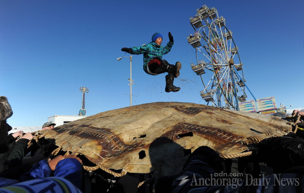 Mason Schrage, 11, flies through the air after being launched during the blanket toss at the Fur Rondy carnival area in downtown Anchorage on Sunday, Feb. 23, 2014.