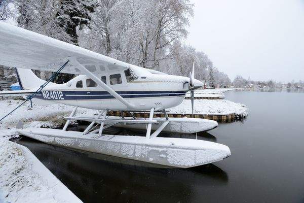 A floatplane rests in a slip as a thin skim of ice forms around it along Lake Shore Drive at Lake Hood Seaplane Base in west Anchorage, Alaska, on Friday, October 21, 2016. The first snowfall of the year covers the trees in the background. (Bob Hallinen / Alaska Dispatch News)