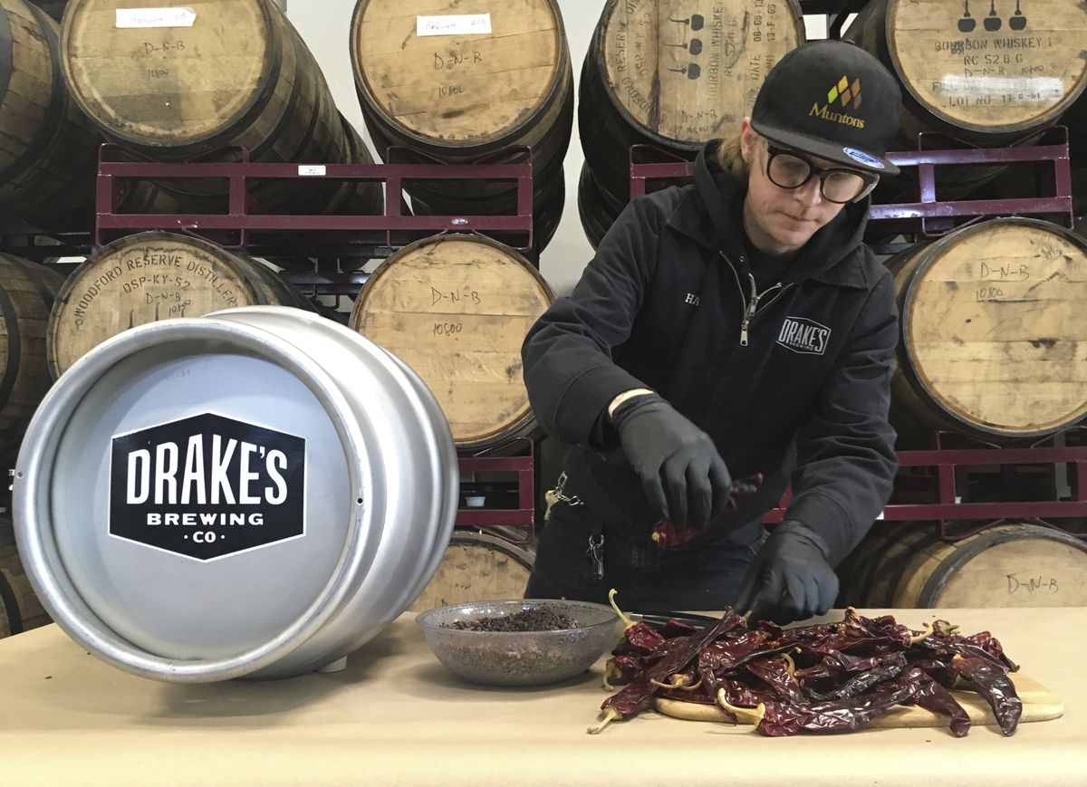 In this photo taken May 10, 2019, Hal McConnellogue, cellar manager at Drake's Brewing Company, works on putting chipotle peppers into a cask used to infuse beer with unique flavors in San Leandro, Calif. (AP Photo/Haven Daley)