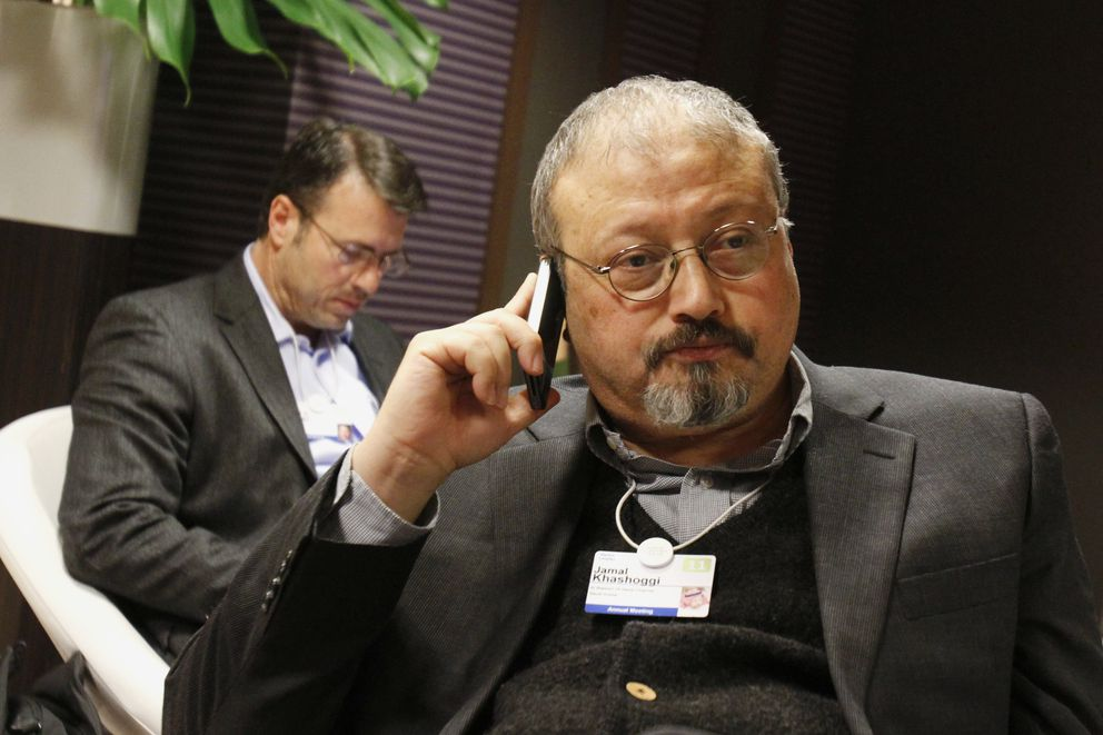 """FILE - In this Jan. 29, 2011 file photo, Saudi journalist Jamal Khashoggi speaks on his cellphone at the World Economic Forum in Davos, Switzerland. Eighteen days after Khashoggi disappeared, Saudi Arabia acknowledged early Saturday, Oct. 20, 2018, that the 59-year-old writer has died in what it said was a """"fistfight"""" inside the Saudi consulate in Istanbul. (AP Photo/Virginia Mayo, File)"""