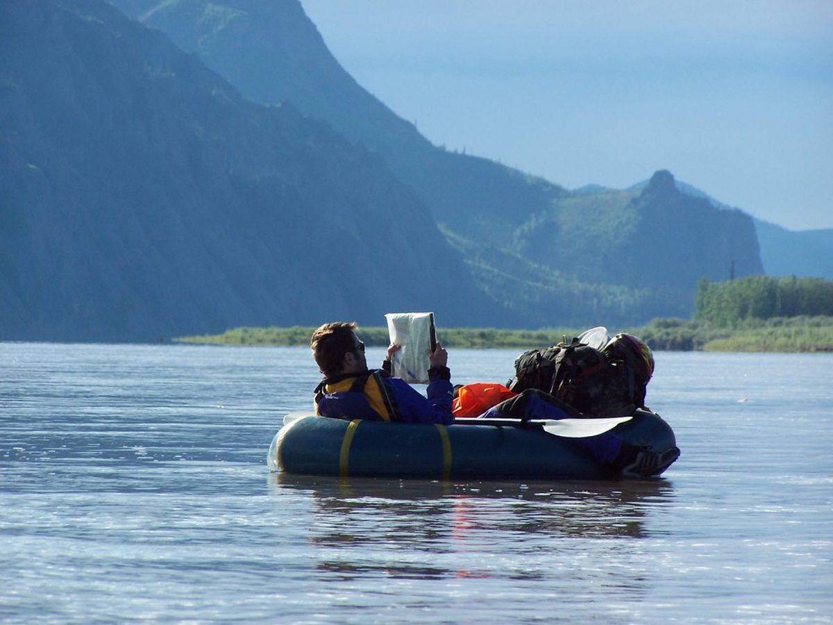 Checking maps to make sure the boater does not pass the town of Circle while packrafting the Yukon River. (Kyle Joly)
