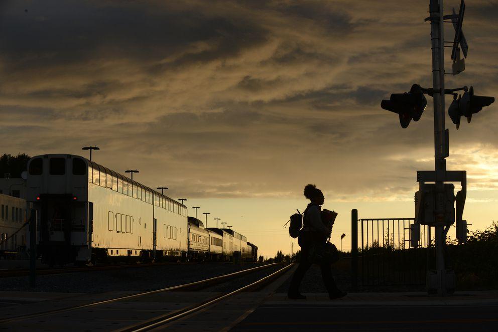 A pedestrian walks along North A Street past an Alaska Railroad passenger train near the Anchorage depot at sunset in Anchorage, AK on Thursday, August 16, 2018. (Bob Hallinen / ADN)