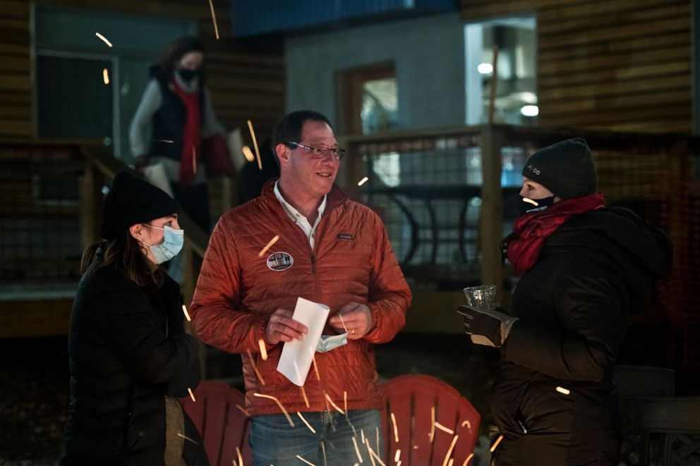 U.S. Senate candidate Al Gross, center, speaks with AFL-CIO political director Joelle Hall in his South Anchorage yard on Election Night, November 3, 2020. Campaign worker Blake McGill is at left. (Marc Lester / ADN)